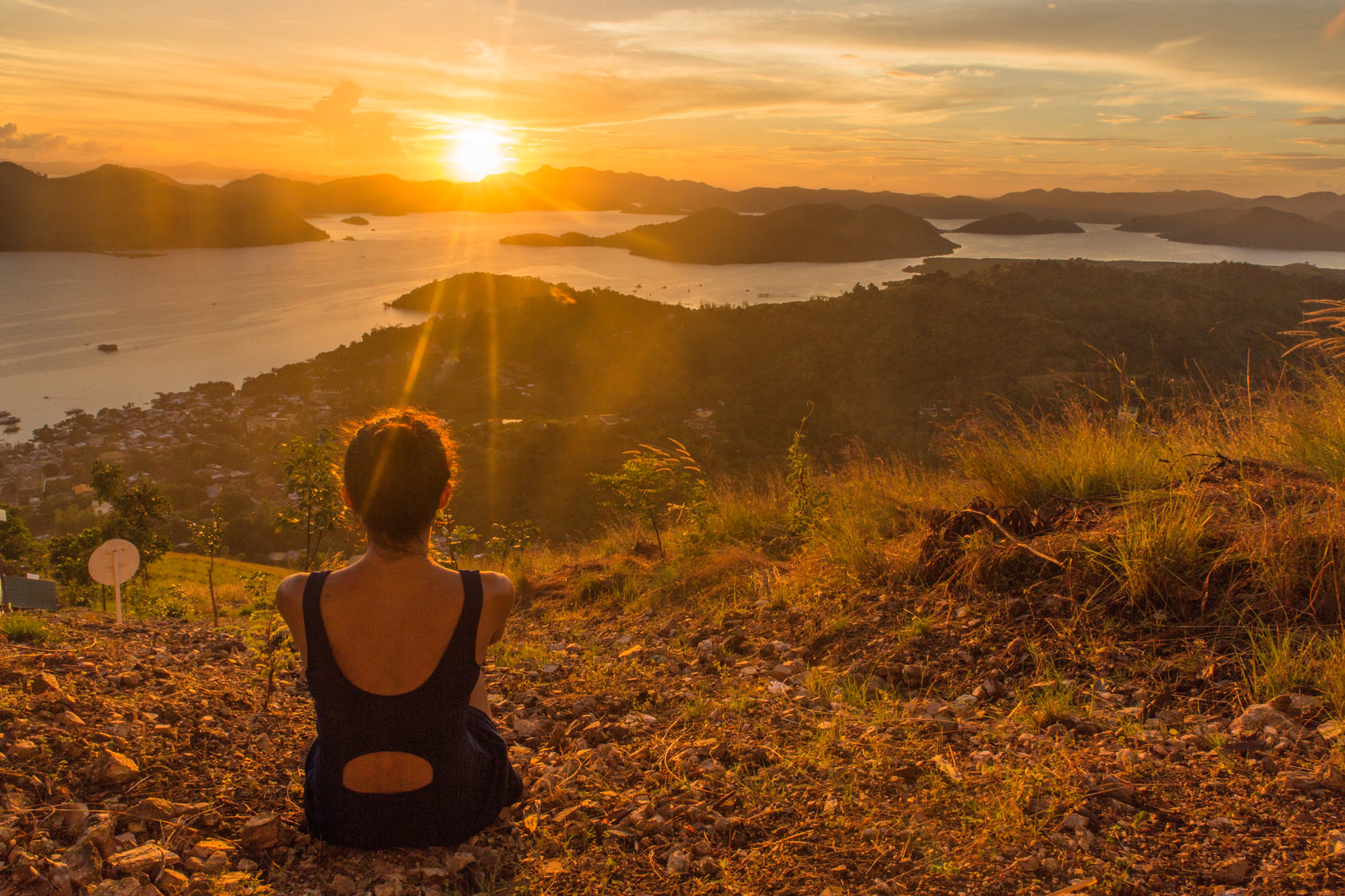 backview of girl, sitting on the earth and observing sunset in Coron Town view point with sea and sky on the background in Philippines, Palawan