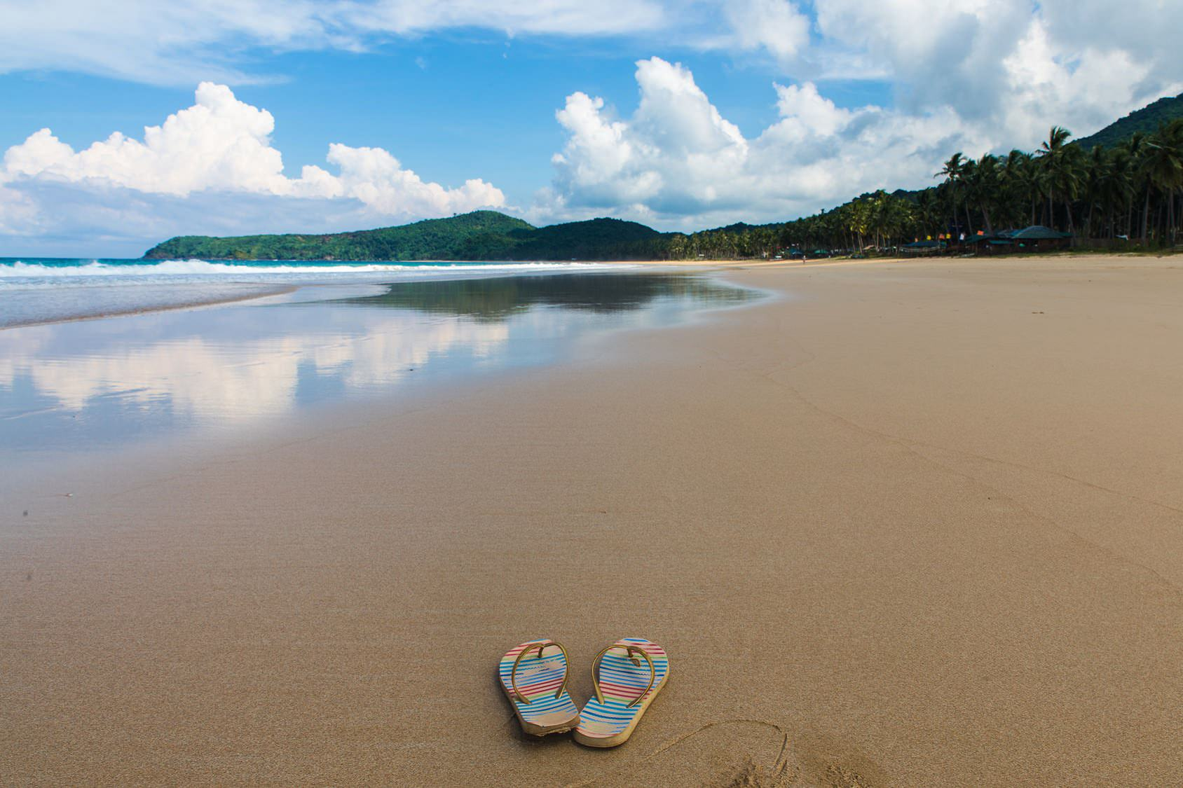 pair of flipflops at Nacpan Beach with cloudy sky and tropical trees on background in El Nido, Palawan province, Philippines